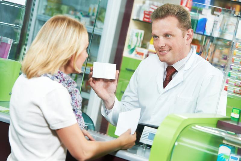 Aptekarz pokazuje lek pacjentce. Uśmiecha się