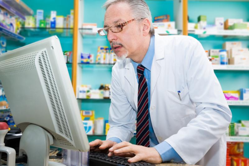 Farmaceuta przy komputerze na tle półek z lekami