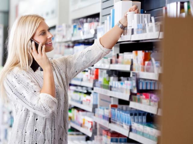 Kobieta rozmawiająca przez telefon, sięga po leki znajdujące się na półkach