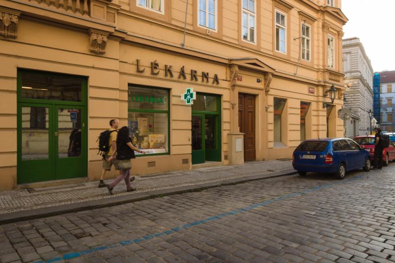 Dwóch przechodniów idzie obok apteki