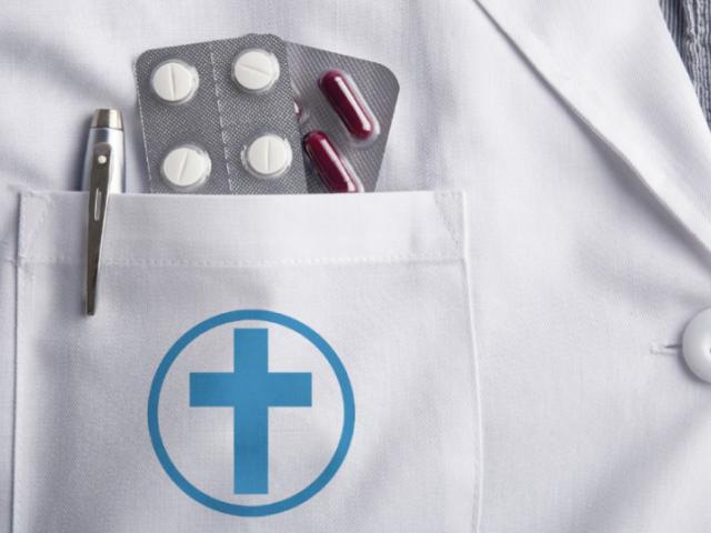 Blistry tabletek i pióro wystające z kieszonki fartucha lekarskiego. Na kieszonce niebieski krzyż w kółeczku
