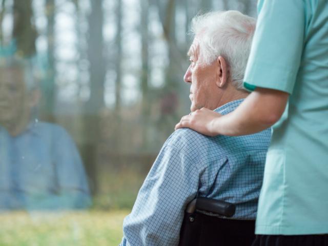 Pacjent siedzący na wózku inwalidzkim patrzy w okno. Za nim stoi pielęgniarka, trzymając ręce na jego ramionach