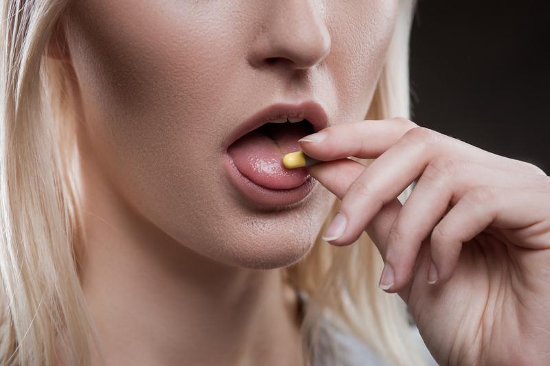 Młoda kobieta wkłada tabletkę do ust.