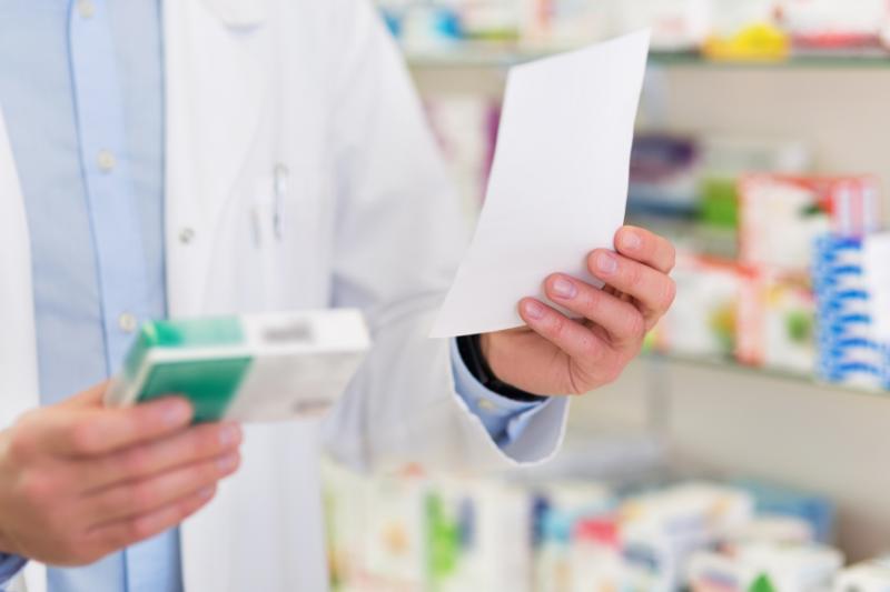 Farmaceuta w ręku lewym trzyma receptę, a w prawym - pudełko z lekiem.