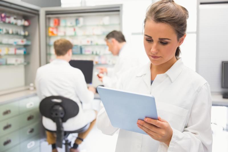Farmaceutka na pierwszym planie, a za nią dwaj farmaceuci przy komputerze.
