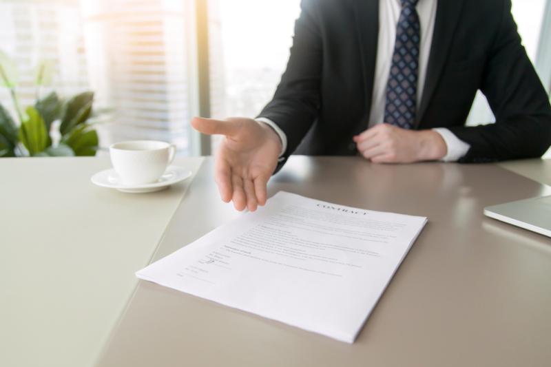 Mężczyzna w garniturze, siedząc za biurkiem wskazuje prawą dłonią na CV leżące przed nim