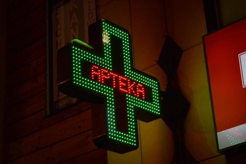 """Szyld apteki w postaci zielonego neonowego krzyża z napisem """"APTEKA""""."""