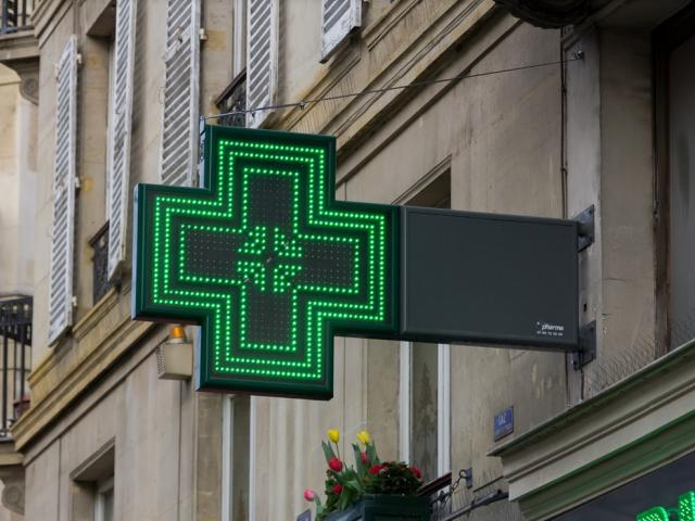 Szyld apteki w postaci zielonego neonowego krzyża