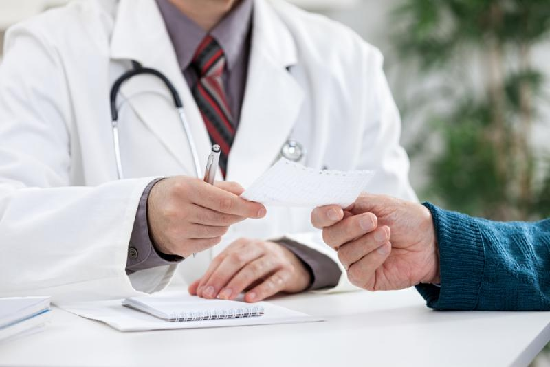 Lekarz przekazuje pacjentowi receptę papierową.